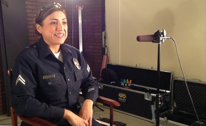Officer Liz Reyes of LAPD seated in a director's chair